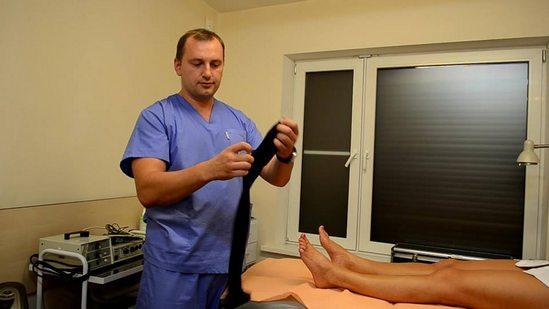 Доктор одевает пациенту компрессионные чулки